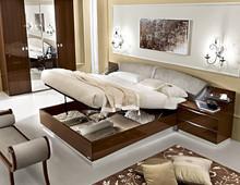 Sypialnia ONDA to nowoczesna włoska sypialnia. Na zdjęciu przedstawione jest łóżko z pojemnikiem na pościel z wezgłowiem tapicerowanym o...