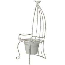 Niebywale dekoracyjny kwietnik w kształcie białego, ażurowego krzesła. Całość wykonana z metalu, a na szczycie konstrukcji siedzi mały ptaszek....