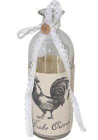Szklana butelka dekoracyjna ozdobiona koronkową wstążką z guzikiem imateriałową opaską z narysowanym kogutem. Butelka może znaleźć swoje...