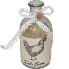 Szklana butelka dekoracyjna ozdobiona koronkową wstążką z guzikiem i opaską z tkaninyz narysowaną kurą. Butelka może znaleźć swoje miejsce w...