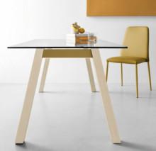 T-TABLE to prostokątny stół z drewnianymi nogami, pomalowaną cylindrycznie metalową poprzeczką i szklanym blatem. T-table posiada kwadratowy...